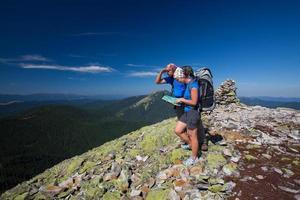 casal caucasiano leva o resto no topo da montanha foto