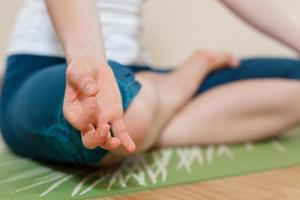 mulher caucasiana está praticando ioga no estúdio (ardkhapadmasana) foto