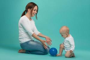 jovem mãe atraente caucasiana sorridente, brincando com bebê fofo