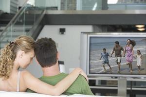 retrato de uma jovem mulher caucasiana com homem assistindo televisão foto