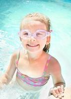 menina bonitinha na piscina em copos foto