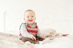 menino pequeno joga no estúdio branco foto