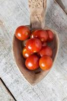 tomate cereja em uma colher sobre fundo de madeira foto