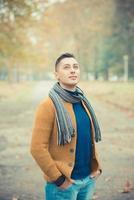 jovem homem bonito caucasiano no parque outono foto