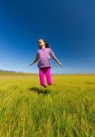 garota feliz pulando em um prado foto