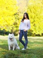 proprietário de mulher feliz e cachorro andando no parque foto
