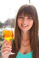jovem mulher sorridente bebendo aperol na blusa turquesa foto