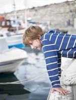 rapaz olhando a água no porto foto