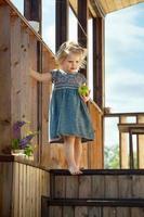 jovem com maçã nas escadas de madeira da casa de campo foto