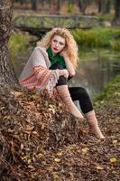 menina loira, vestindo blusa verde e xale grande posando ao ar livre