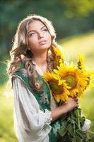 linda loira com buquê de flores amarelas brilhantes