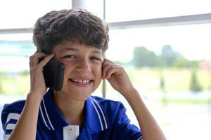 menino sorridente, falando no celular foto
