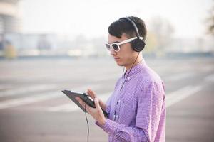 jovem louco asiático engraçado no estilo de vida ao ar livre da cidade ouvindo foto