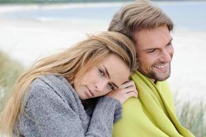 casal abraçando uns aos outros na praia, mar de outono, grama do mar foto