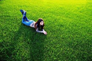 mulher feliz, deitado na grama verde foto