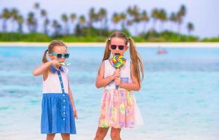 meninas adoráveis com pirulito na praia tropical foto