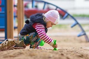 litle menina brincando com areia na areia foto
