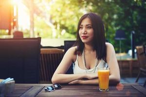 linda mulher asiática, aproveitando o dia de verão no restaurante moderno foto
