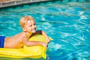 garoto relaxando e se divertindo na piscina