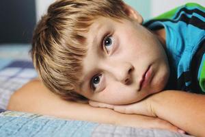retrato de um menino que pensa em uma cama foto