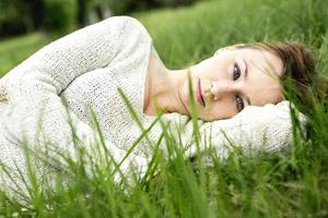 linda garota deitada na grama foto