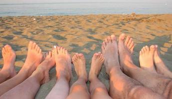 com os pés descalços de uma família na costa do mar foto