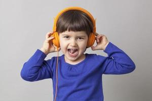 feliz menina pré-escolar de 4 anos desfrutando de um som estéreo groovy
