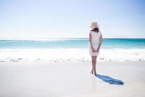 linda morena usando chapéu de palha e andando na água foto