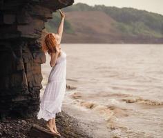 mulher de vestido branco em pé na praia.