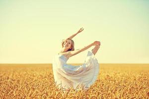 mulher jovem feliz, curtindo a vida no campo de trigo dourado foto