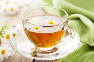 xícara de chá de ervas com flores de camomila foto