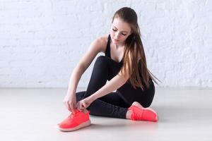 menina esportiva ativo instrutores de laço sapatos esportivos amarrar cadarços foto