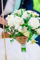 bouquet de noiva e mãos da noiva e do noivo foto