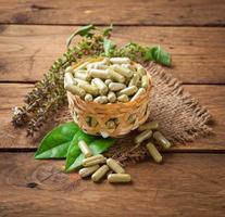 cápsula de ervas com folhas de ervas verdes na madeira foto