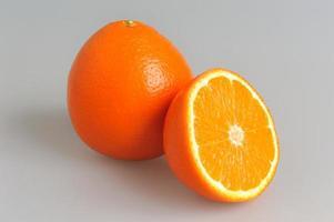 metade e laranja inteira em fundo cinza foto