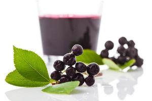 chokeberries, copo com suco de aronia foto