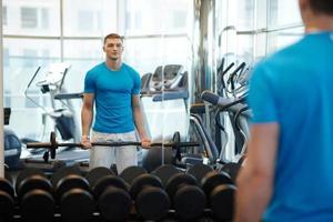 homem fazendo exercícios com barra foto