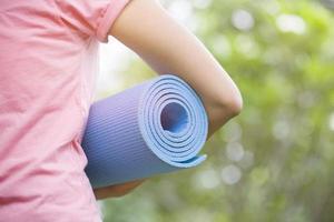 jovem mulher segurando um tapete de ioga