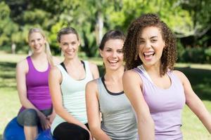 grupo de aptidão sentado nas bolas de exercício foto