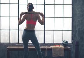 vista traseira, de, mulher segura toalha, ombros ombros, em, ginásio foto