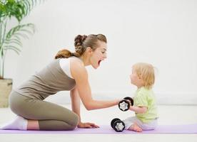 bebê, ajudando, mãe, levantamento, dumb-bells foto