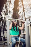 garota fazendo ombro pressione ao ar livre foto