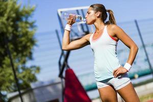 jovem atleta bonita água potável após o exercício foto