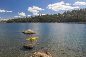 mulher de caiaque no lago de montanha bonita. foto