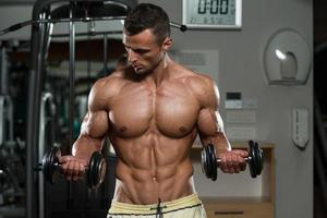 fisiculturista exercitar bíceps com halteres foto