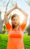 mulher ativa fazendo poses de ioga ao pôr do sol foto