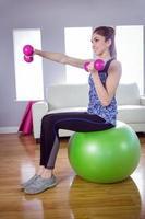 cabe mulher levantando halteres na bola de exercício foto
