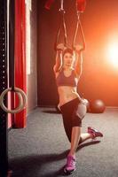 um treinamento de ginástica mulher com tiras trx no quarto escuro foto