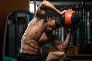 treino de homem atlético com bola médica foto