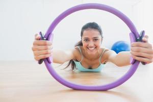 mulher sorridente com anel de exercício no estúdio de fitness foto